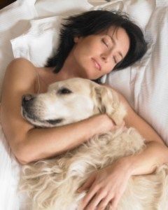 woman sleeping with arms wrapped around golden retriever